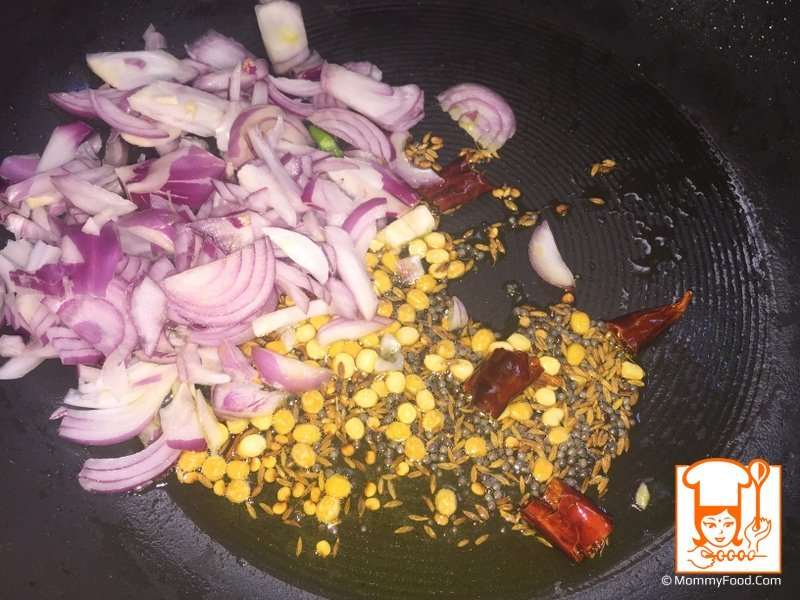 Step 4: When mustard seeds make a crackling sound, add sliced onions, curry leaves, green chillies and salt. Saute for a minute