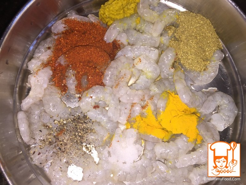 Add and mix 1 tbsp red chilly powder, 1 tbsp ginger garlic paste, 1/4 tbsp salt, 1/2 tbsp turmeric powder, 1 tbsp coriander powder to prawns.